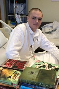 Chris with his first batch of books, in the hospital.